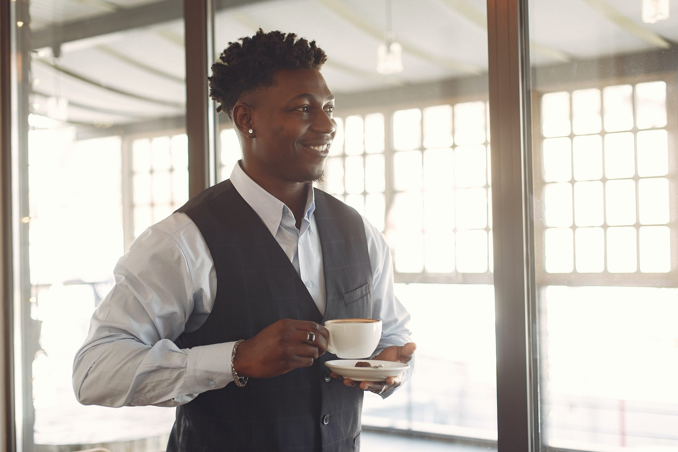 smiling young ethnic man drinking coffee in cafe near window 3873735 scaled